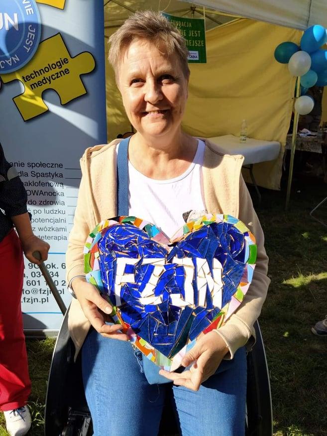 Kobieta w krótkich włosach siedzi na wózku, trzyma serce o wymiarach ok. 40x30cm. Na środku serca wyklejone białymi szkiełkami litery FZJN, na niebieskim tle. Brzegi z kolorowych szkiełek